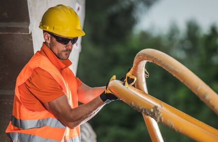 Caucasian Worker with High Voltage Plastic Pipe. Underground Electric Line Installation. Construction Industry.