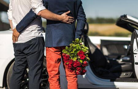 Same SexRelationship. Gay Couple in Front of a Car. One Men with Bouquet of Red Roses.