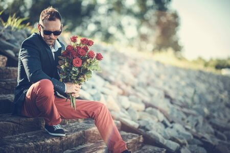 Caucasian Men in His 30s Awaiting His Date While Seating on the Concrete Stairs with Bouquet of Fresh Cut Red Roses.