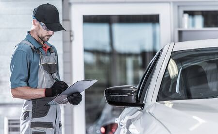 Caucasian Car Service Worker Making Documentation About Vehicle Issues. Car Maintenance In the Authorized Service Center. Imagens