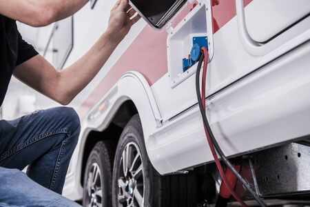 RV Park Electric Hookup. Caucasian Men in His 40s Connecting His Travel Trailer Recreational Vehicle to Park Electric Installation. Stock Photo