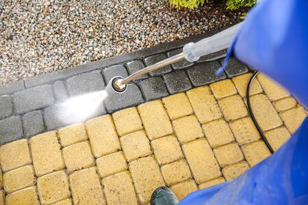 Driveway Bricks Pavement Washing Using Pressure Washer. Closeup Photo.