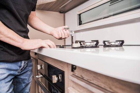 Camper Van Stove Repair by Caucasian Professional RV Technician in His 40s. RV Industry Concept. Appliances Maintenance. Stock Photo