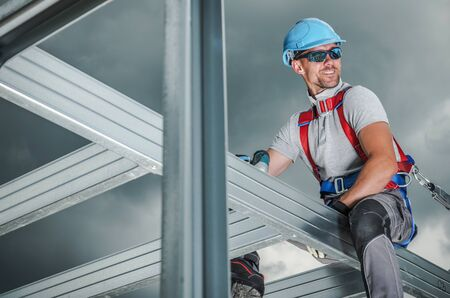 Smiling Construction Contractor Wearing Safety Harness. Caucasian Worker in His 30s. Skeleton Steel Building Frame.