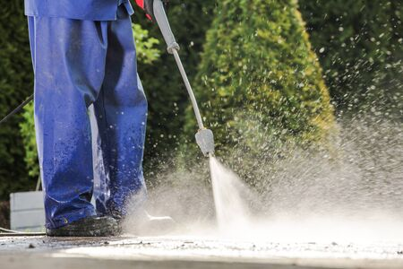 Caucasian Men Washing House Driveway Using Pressure Washer. Cleaning Technologies.