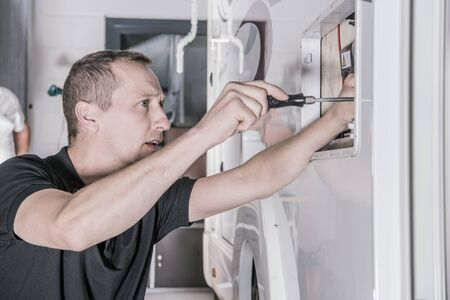 Camper Van RV Refrigerator Repair. Motorhome Appliances Maintenance. Caucasian RV Technician with Screwdriver Looking For Potential Issues Inside Outside Camper Compartment. Automotive and Travel Industry Theme.