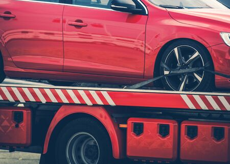 Compact Modern Car Towed Away on Red Towing Truck. Closeup Photo. Automotive and Transportation Industry. Reklamní fotografie