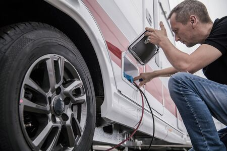 Caucasian Technician Trying To Fix RV Travel Trailer Electric Hookup Problem Looking Inside Outside Compartment.