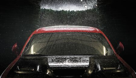 Automotive Concept. Car in a Car Wash at Night. Automatic Washing Modern Vehicle.