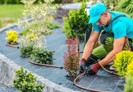 Professionele blanke tuinman bouwt irrigatiesysteem voor planten in ontwikkelde tuin. Industrieel thema.