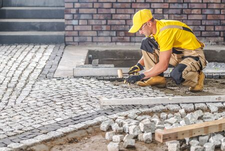 Professional Caucasian Worker Building Granite Paved Hardstanding Garden Path. Industrial Theme.