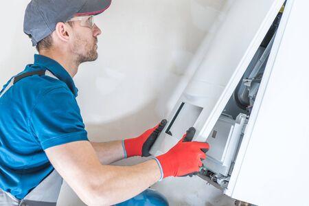 Réparation d'unité de chauffage de maison par un technicien professionnel. Photo en gros plan. Problèmes d'équipement domestique.