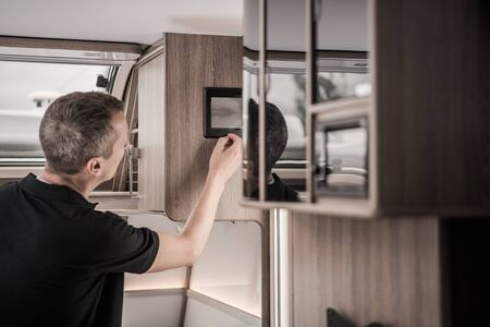 Recreational Vehicle RV Computer Data Display. Caucasian Men in His 40s Checking Black and Gray Tanks Level Using On Screen Information Inside His Modern Travel Trailer. Stock Photo - 130051556