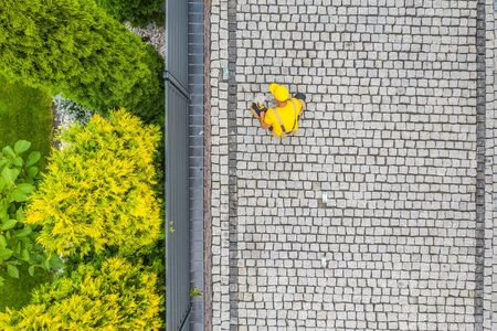 Residential Bricks Driveway Building. Caucasian Construction Worker Finishing Granite Decorative Brick Road. Stockfoto