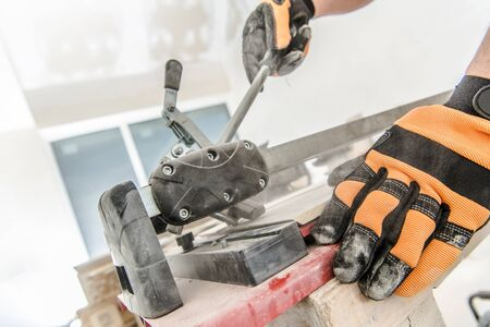 Tile Cutter Industry Equipment. Construction Worker Trimming Ceramic Tiles. Industrial Theme.