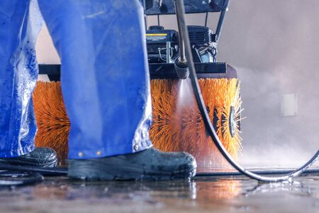 Pressure Washing Work. Men Cleaning His Brush Cleaner Using Powerful Water Stream. Stockfoto