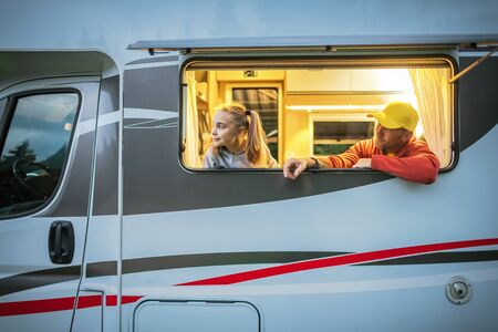 Caucasian Family, Father and Daughter Looking Outside the Window From Their RV Camper Van While on the Motorhome Road Trip. Exploring the World From the Motorcoach.