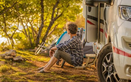 Retired Woman in Her 60s Enjoying Her Vacation with Camper Van. Senior Outdoor Recreation Theme.