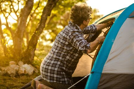 Caucasian Retired Woman in Her 60s Enjoying Summer Vacation on the Go with Small Tent. Retirement Theme.