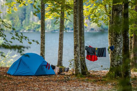Wilderness Tent Camping. Blue Modern Tent and Drying Clothes on a Rope Between Forest Trees. Outdoor Campsite at the Lake.