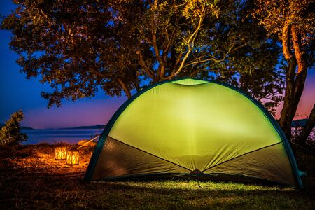 Sea Front Tent Camping. Glowing Light Inside Small Modern Tent. Campground and Outdoor Theme.