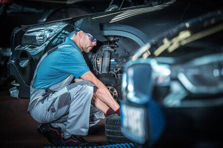 Caucasian Car Mechanic and His Automotive Job. Auto Service Shop. Servicing Modern Vehicle Brakes. Stok Fotoğraf