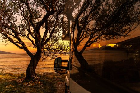 Scenic Sea Front RV Park Camping Pitch with a Tree During Sunset. Motorhome Summer Vacation Road Trip.