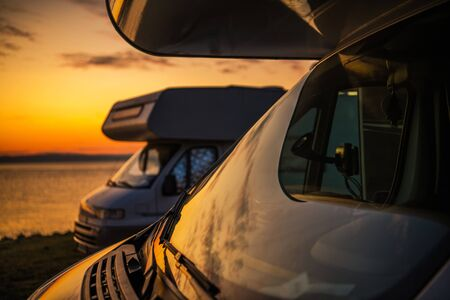 RV Camper Vans Camping. Two Motorhomes and the Scenic Sunset. Closeup Photo. Summer Vacation on the Road. Travel Theme.