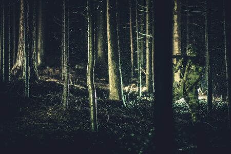 Special Forces Soldier on Duty in Dense Forest at Night During Having Rainfall. Military Theme.
