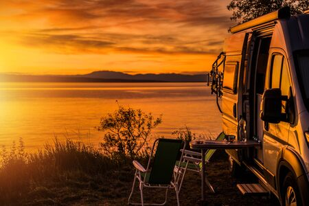 Class B Motorhome RV and the Scenic Sea Front Sunset. Road Trip Camping. Recreation Vehicle Theme. Stok Fotoğraf