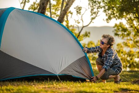 Summer Vacation in a Tent. Retired Caucasian Woman in Her 60s Preparing Her Tent Checking Material Tension.