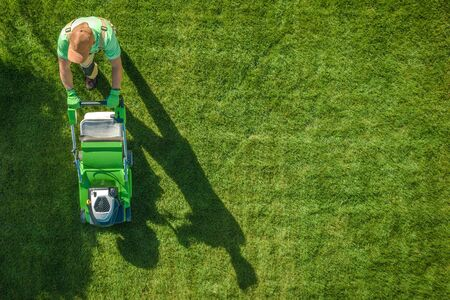 Lawn Moving Aerial Photo. Caucasian Gardener with Gasoline Grass Mower at Work. Landscaping Business. Industrial Theme.