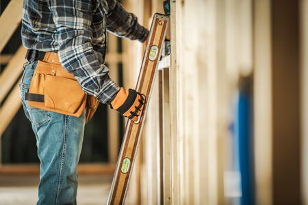 Contractor Worker Taking Spirit Level Tool to Make Sure the Wooden Frame Alignment is Correct. Construction Tools and Building Technologies.
