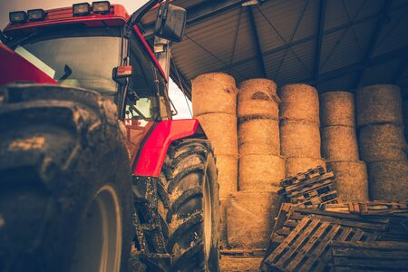 Agriculture Heavy Equipment. Tractor and the Barn Full of Hay Bales. Industrial Theme.