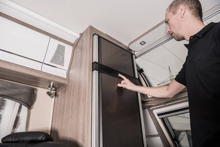 RV Motorhome Refrigerator Check by the Owner. Preparing Recreational Vehicle For the Season. Travel Trailer Interior.