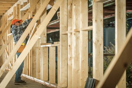 Wooden House Construction Job. Caucasian Contractor Carpenter Finishing Building wood Beams Frame. Industrial Theme.