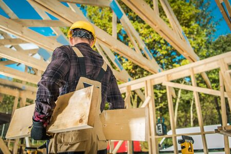 Caucasian Construction Worker Moving Wood Elements. Wooden Building Frame in the Background. Industrial Theme.