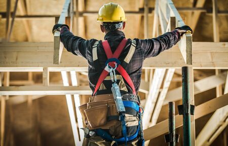 Wood House Construction Challange. Caucasian Carpenter Contractor Wearing Safety Harness in Front of New Developed wood Frame Home. Construction Industry. Stok Fotoğraf