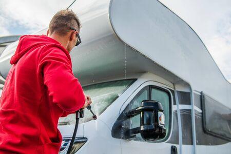 Caucasian Men Washing His Motorhome RV Class C Camper Van Using Pressure Washer. Travel Industry Theme.