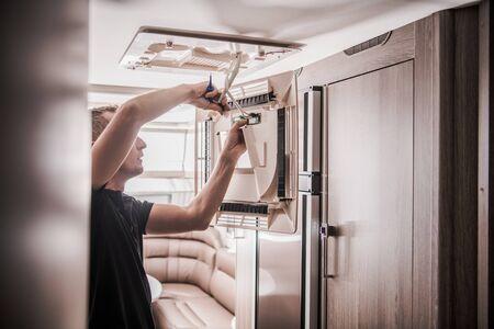 Broken RV Air Condition Unit Repair by Professional Technician. Travel Trailer Appliances. Travel Industry Theme. Stok Fotoğraf