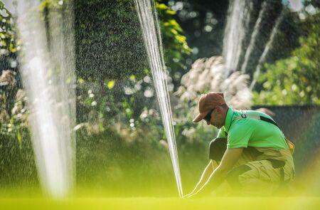 Garden Watering System Installation. Caucasian Worker Adjusting Water Sprinkler. Gardening Technologies. Stok Fotoğraf