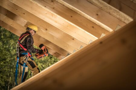 Professional Carpenter Contractor Job. Caucasian Worker with Nail Gun and the Wooden House Roof Frame. Industrial Theme. Stok Fotoğraf