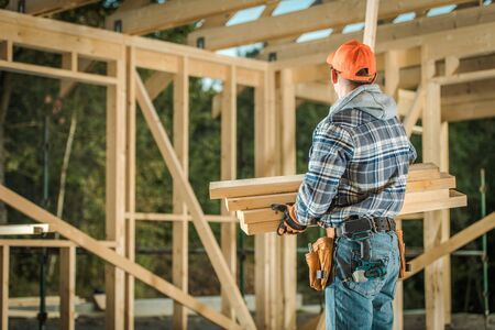 Caucasian Professional Carpenter with Wood Elements. Residential Building Wooden Frame Construction.