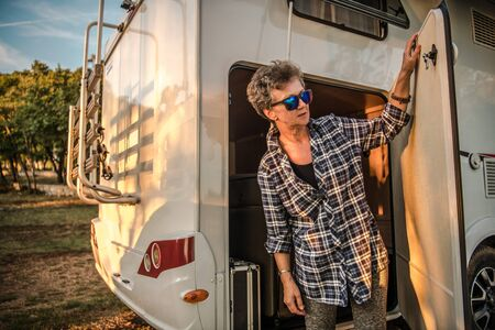 Retired Caucasian Woman in Her 60s on the Motorhome RV Road Trip. Moving Stuff From the Camper Van Cargo Section. Travel Industry.