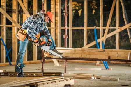 Construction Contractor Worker Cutting Wooden Frame Elements Using Professional Chainsaw. Caucasian Men in His 30.
