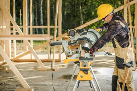 House Construction Worker Cutting Wooden Frame Elements Using Professional Circular Saw. Caucasian Men in His 30 Wearing Hard Hat.