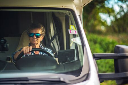 Caucasian Retired Woman in Her 60s Driving Class C Motorhome. Summer Road Trip.