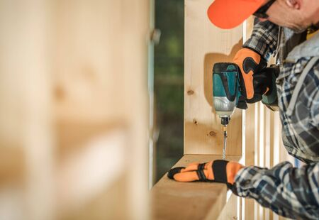 Caucasian Contractor in His 30s with Drill Driver Attaching Wooden Frame Elements. Wood Frame House Construction.  Stock Photo