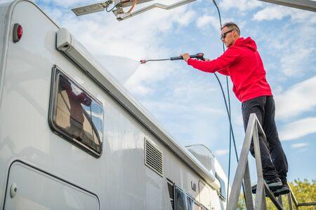Post Season RV Motorhome Camper Van Washing Using Pressure Washer. Caucasian Motor Coach Owner.