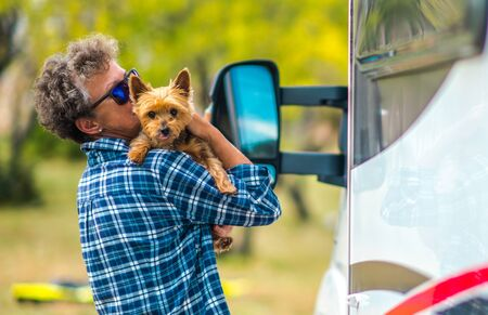 Retired Caucasian Woman with Her Dog. Australian Silky Terrier on the RV Camper Van Road Trip. Traveling with Pets.